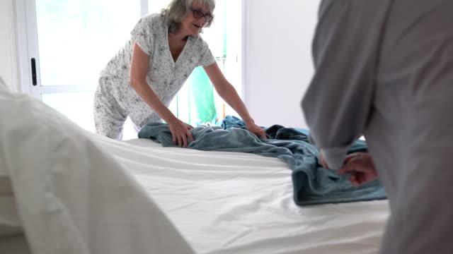 Mature couple making the bed together Mature couple making the bed together. They are helping each other. They are wearing pajamas and just woke up. chores stock videos & royalty-free footage