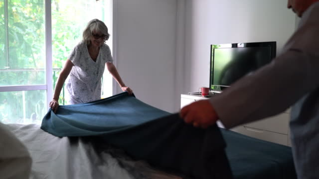 mature couple making the bed together - para aranżacja filmów i materiałów b-roll