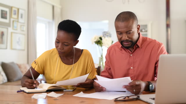 Mature couple managing home finance Cheerful mature couple sitting and managing expenses at home. Happy african man and woman paying bills together and managing budget. Black smiling couple checking accountancy and bills while looking at each other. finance stock videos & royalty-free footage