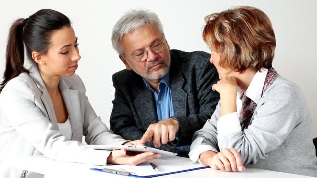 vídeos de stock e filmes b-roll de casal maduro com consultor financeiro de reunião - senior business woman tablet