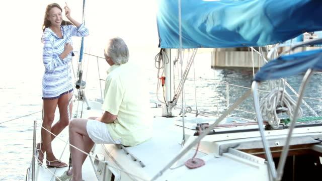 vídeos de stock, filmes e b-roll de casal maturo no convés do barco à vela, conversando, rindo - marina