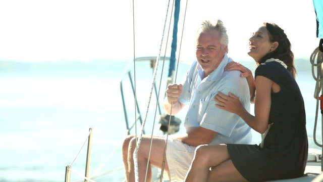 mature couple on deck of sailboat, talking, relaxing - quarantenne video stock e b–roll