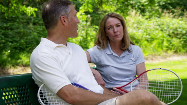 Mature couple outdoors take a break from playing tennis video