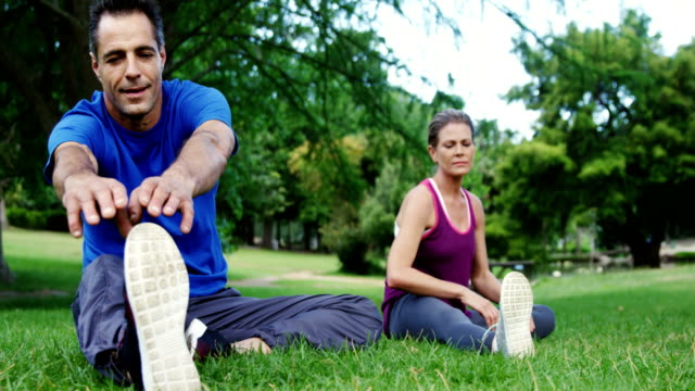 mature couple performing stretching exercise in the park - 35 39 anni video stock e b–roll