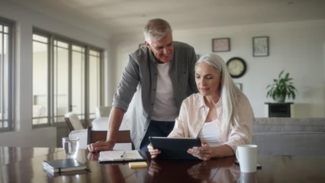 vídeos de stock e filmes b-roll de mature couple planning expenses at home - bills couple