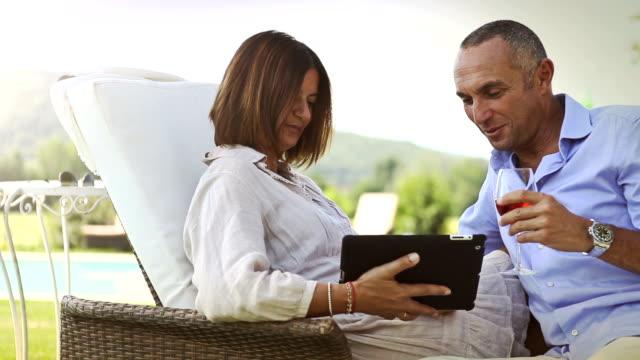 Mature couple planning summer vacation on laptop video