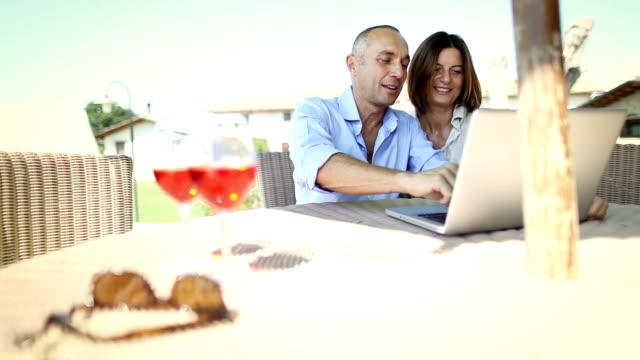 coppia matura alla pianificazione vacanze su computer portatile - quarantenne video stock e b–roll