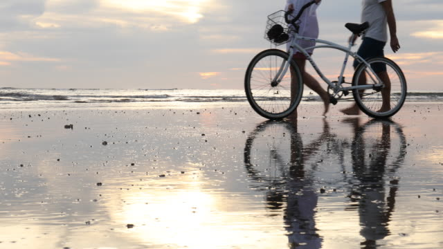 Mature couple push bicycle along tidal flat at sunrise Gentle surf and ocean waves in distance lockdown viewpoint stock videos & royalty-free footage
