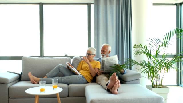 stockvideo's en b-roll-footage met volwassen paar lezen tijdschriften en het hebben van een gesprek. - woman home magazine