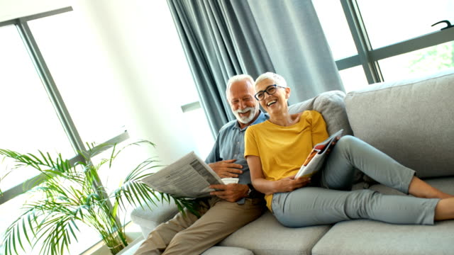 mature couple reading magazines and relaxing. - capelli grigi video stock e b–roll