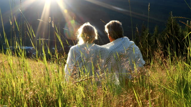 Mature couple relax in grasses, look out over mountains