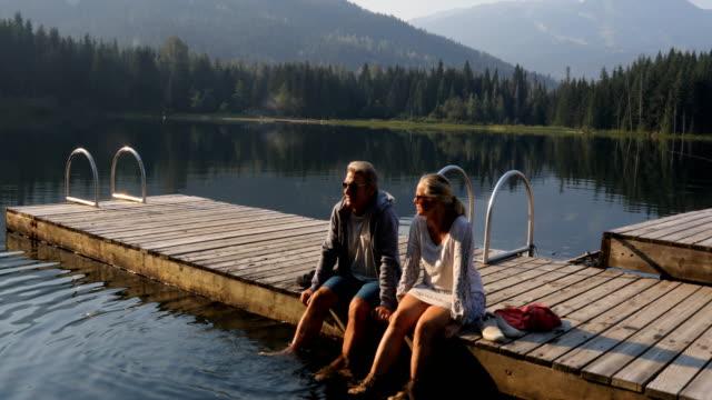 vídeos y material grabado en eventos de stock de pareja relajarse en el muelle durante el amanecer de la montaña - viaje a canadá