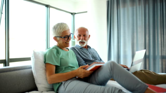 Mature couple relaxing in bed. Closeup of mid 60's couple browsing through some web pages while relaxing in the bedroom. short hair stock videos & royalty-free footage