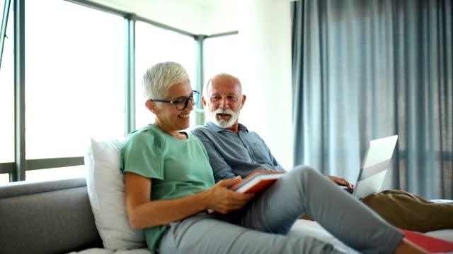 mature couple relaxing in bed. - krótkie włosy filmów i materiałów b-roll