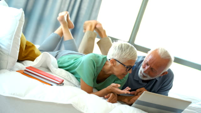 mature couple relaxing on bed and using a laptop. - capelli grigi video stock e b–roll