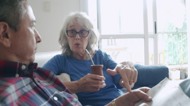 Mature couple sitting together on the sofa at home, doing crosswords puzzles. They are talking and drinking yerba mate together.