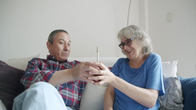 Mature couple sitting together on the sofa at home. They are talking and drinking yerba mate together. video