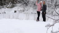 istock Mature couple take pics in snowy forest setting 1196851652