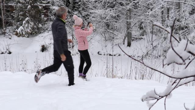 vídeos y material grabado en eventos de stock de pareja madura tomar fotos en el entorno del bosque nevado - memorial day weekend