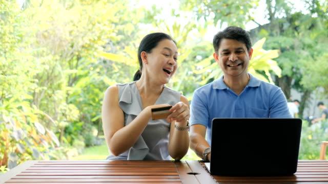 Couples matures utilisant l'ordinateur portatif pour payer des factures - Vidéo