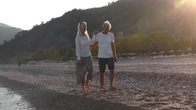 mature couple walk along empty beach at sunrise - pantaloncini video stock e b–roll