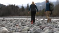 istock Mature couple walk along stream bed, with boulders 1214541252