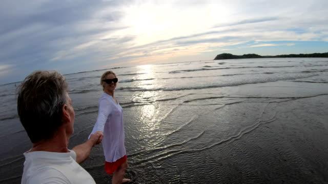 성숙한 부부는 일출에 조수 플랫을 따라 산책 - 10초 이상 스톡 비디오 및 b-롤 화면