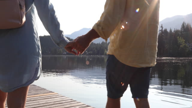 mature couple walk along wooden lake pier at sunrise - pantaloncini video stock e b–roll