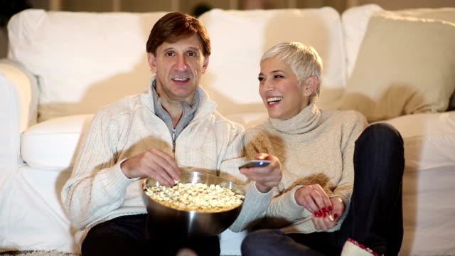 coppia matura guardando la tv per natale - christmas movie video stock e b–roll