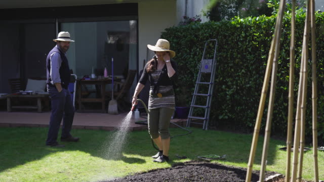 Mature couple water small garden in their backyard of house Moments at home with mature couple living at home, working on garden, using technology. pedal pushers stock videos & royalty-free footage