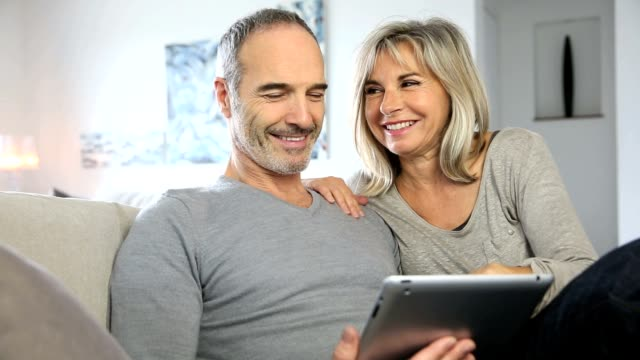 Mature couple websurfing with tablet video