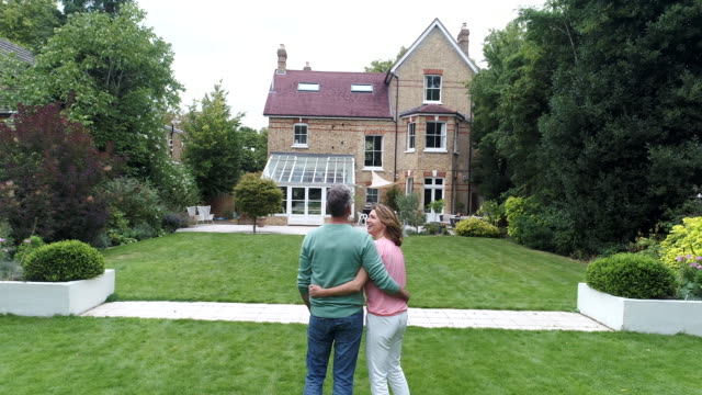 mature couple with arms around each other looking at house and view of building exterior - grandangolo tecnica fotografica video stock e b–roll