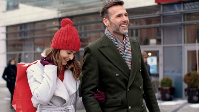 Mature couple with shopping bags walking the street