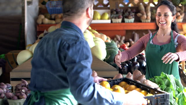 Mature couple working at produce stand A mature couple working together to set up a produce stand at a farmer's market. The man hands to woman a crate of oranges. owner stock videos & royalty-free footage