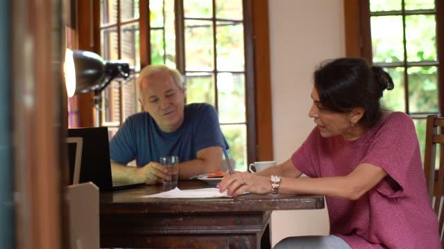 vídeos de stock e filmes b-roll de mature couple working together at home - bills couple