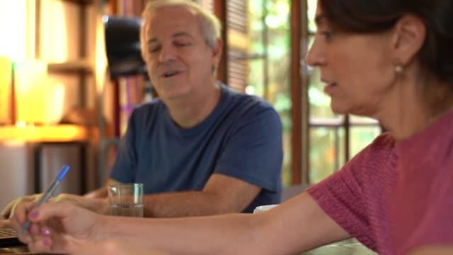 vídeos de stock e filmes b-roll de mature couple working together at home - 55 59 anos