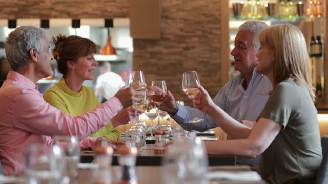 stockvideo's en b-roll-footage met oudere paren roosteren bij maaltijd - dineren