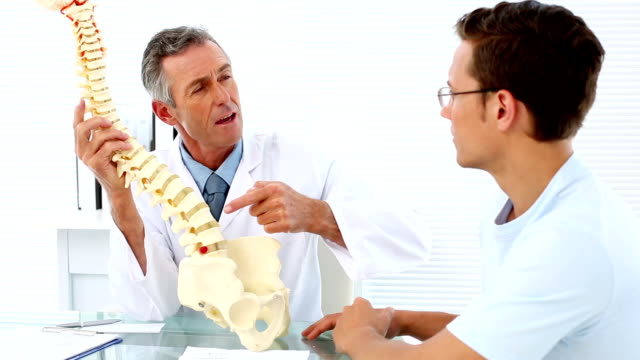 Mature doctor speaking to his patient about model of spine video