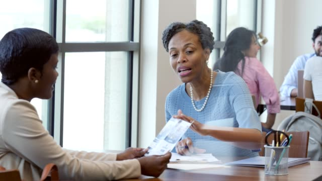 Mature female bank employee explains bank services to new client