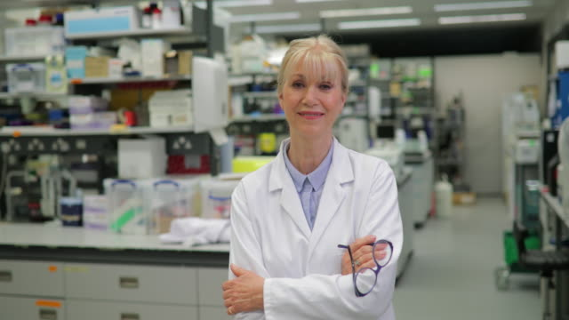 Mature Female Bio Chemist in a lab A portrait of an accomplished female scientist in a lab, she is confident and looking straight to the camera, standing tall and wearing her uniform proudly. lab coat stock videos & royalty-free footage