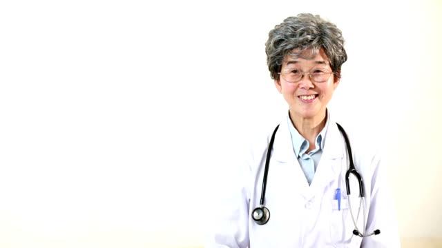 mature female doctor gesturing, smiling, portrait - mature women studio grey hair bildbanksvideor och videomaterial från bakom kulisserna