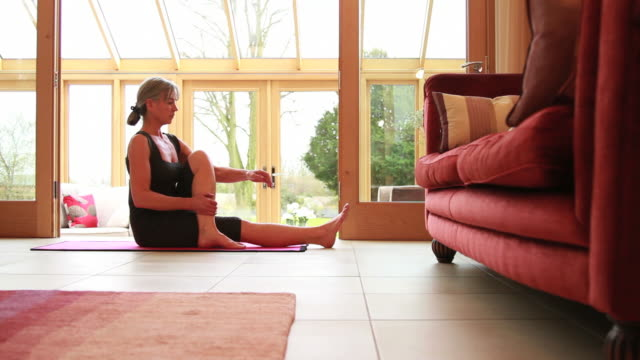 Mature female exercising yoga at home video