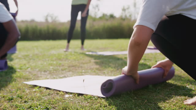 mature female friends rolling up exercise mats on grass at end of outdoor yoga lesson - tappetino video stock e b–roll