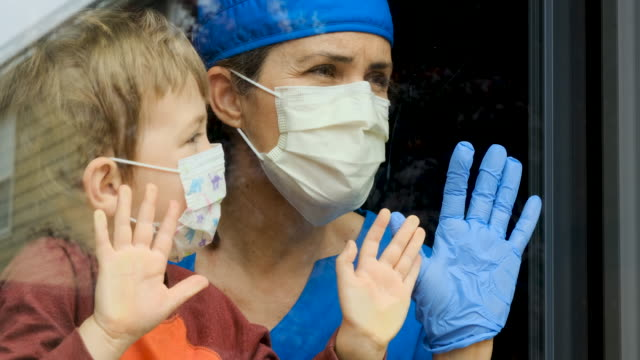Mature female healthcare worker posing with her son, both with protective masks, very sad looking through window worried about Covid-19 lockdown