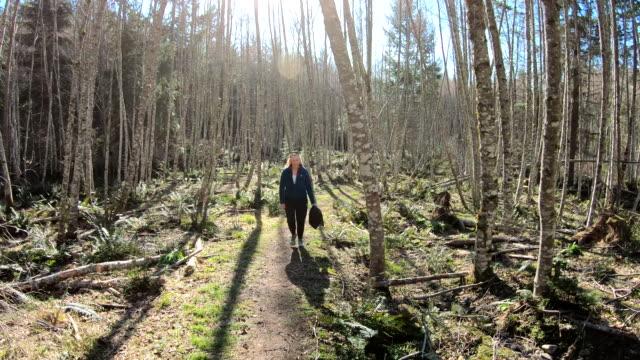 vídeos de stock e filmes b-roll de mature female hiker follows forest path - 55 59 anos