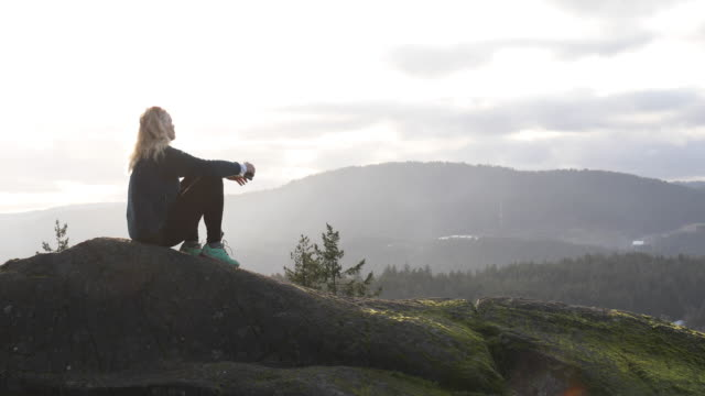 Mature female hiker relaxes on mossy rock spine