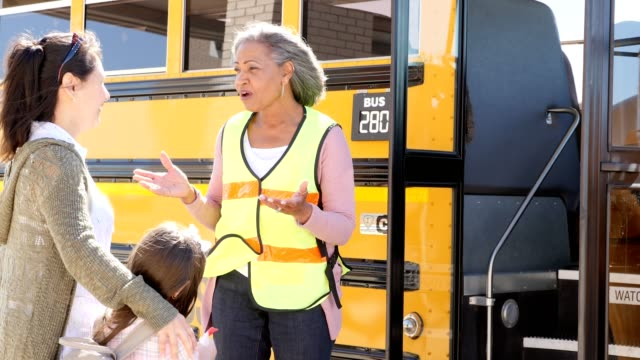 mature female school bus driver reassures a child's mom before the mom's daughter gets on the school bus - bus driver stock videos and b-roll footage
