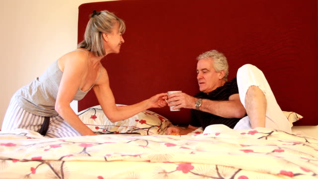 Mature female serving breakfast in bed video