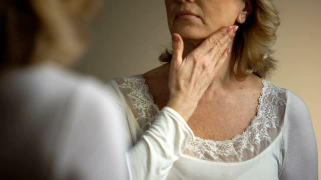 Mature female touching her wrinkled neck in front of mirror, aging process