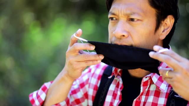 mature filipino man putting on his mask - филиппинского происхождения стоковые видео и кадры b-roll